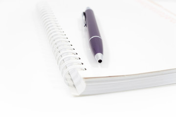 Spiral notebook with pen isolated on white background