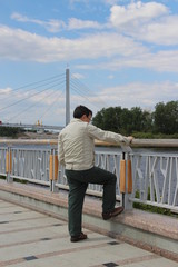 man on the embankment of the river