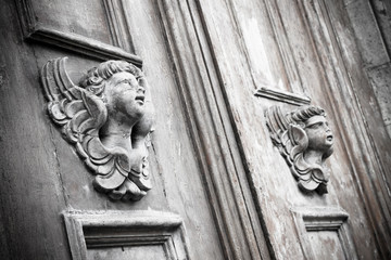 Sculpture of an angel on a wooden door in Italy