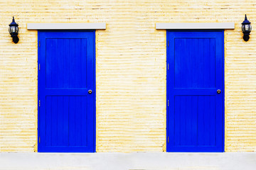 A vintage blue couple doors on brick wall