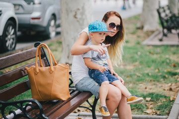 Fashion mother and son walking in a park
