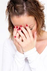 junge Frau vergräbt Ihr Gesicht in den Händen