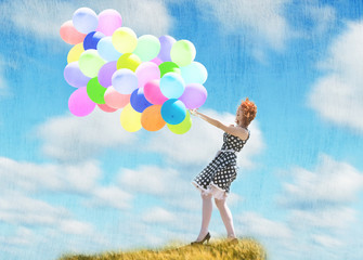 Smiling redheaded girl with balloons in the wind
