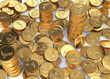 Gold dollar coins spread on a white surface and few stacks.