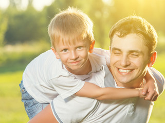 happy Dad and son hugging and laughing in summer nature