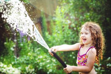 Happy curly girl under water splashes in the summer garden.