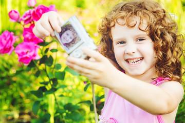 Happy little girl taking self photo on a summer garden.