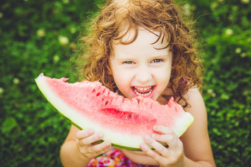 Happy little girl eating watermelon in summer park. Instagram fi