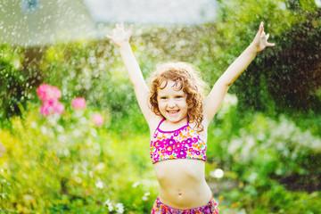 Little girl under water splashes in the summer garden. Toning pf