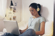 Casual young woman sitting on bed and using laptop at home. - 68483442