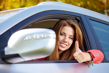 Happy smiling woman with car key. Driving.