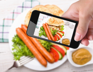 Hands taking photo  sausages and vegetables with smartphone