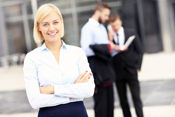 Happy businesswoman standing outside modern building