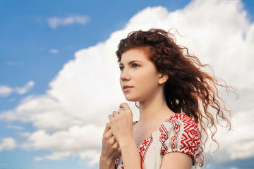 Portrait of dreamy girl on blue sky background