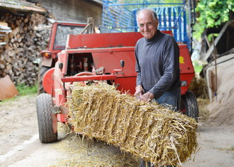 Organic farmer making/stack bales for feeding livestock
