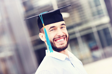 Cheerful graduate outside modern building