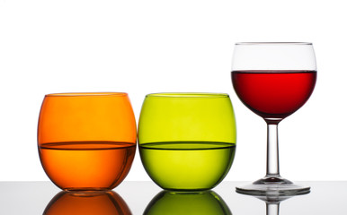 Water and wine - three glasses backlit. White background.