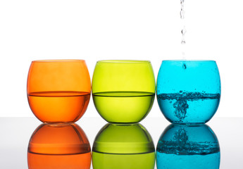 Glasses of water, yellow green, orange, turquoise colours.
