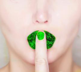 finger on green glossy lips