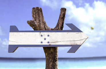 Honduras wooden sign with a beach on background