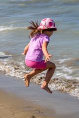 Hüpfendes Mädchen am Strand