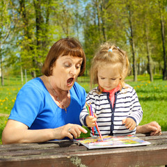 Grandmother and little granddaughter paint outdoors