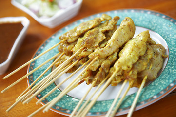 close up yellow indian pork satay in dish