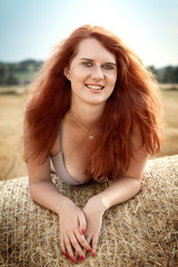 Beautiful redhead on the bale of straw