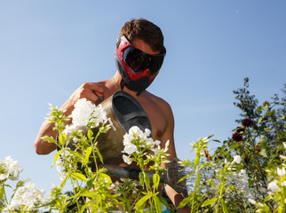 Young man in paintball mask watering the flowers