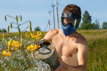 Funny man in paintball mask watering yellow lily