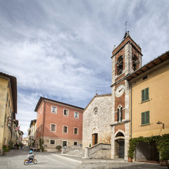 lonely square with old belfry and boy with bicycle