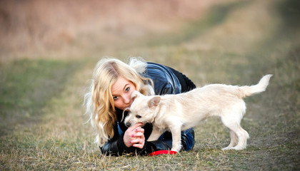 Blond girl playing with her puppy on the field