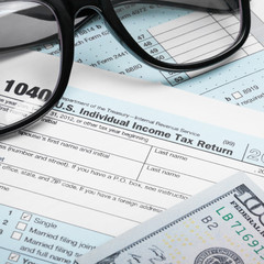 USA Tax Form 1040 with glasses and 100 US dollars - 1 to 1 ratio