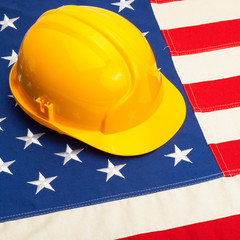 Construction helmet laying over USA flag - 1 to 1 ratio
