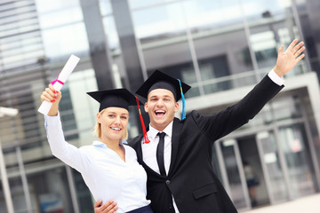 Cheerful graduates outside university