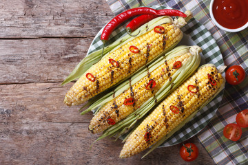 Grilled corn with chili and tomato sauce top view