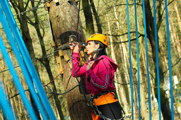 Beautiful positive brunette  engaged climbing the trees.