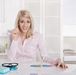 Lachende junge Frau im Portrait: sitzend am Schreibtisch