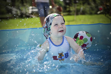 Small boy playing in swimming pool