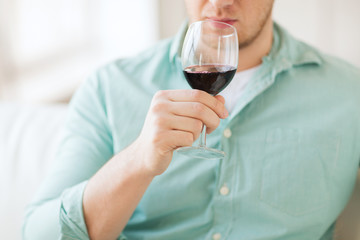 close up of man drinking wine at home
