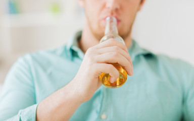 close up of man drinking beer at home