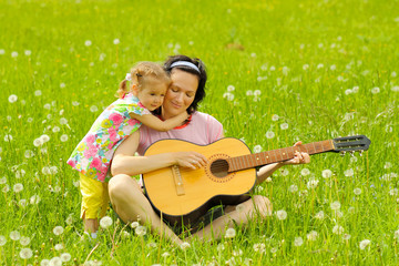 young mother plays the guitar for her daughter