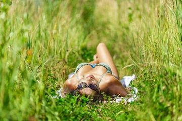 woman sunbathing in bikini on the grass