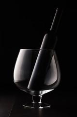 Black glass wine bottle in the huge wine glass