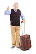 Smiling senior man holding his luggage and giving thumb up