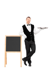 Male waiter holding a tray and leaning on a blackboard
