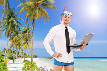 Businessman with a diving mask holding a laptop and standing on