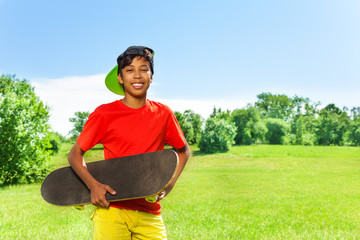 Smiling boy in cap and with skateboard portrait