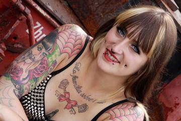 Portrait einer jungen, tätowierten und gepiercten Frau