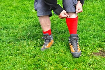 Wanderschuhe und rote Socken anziehen